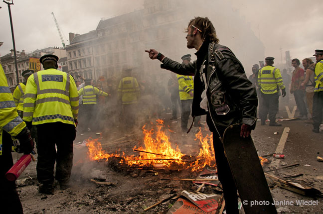 Police putting out fire of burning placards in Parliament Square during Anti-austerity march central London June 20th 2014